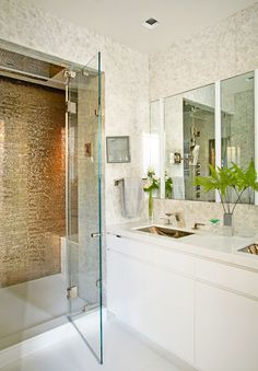 In the master bathroom, the sinks are by Waterworks and the polished white onyx in the shower is by ABC Stone.