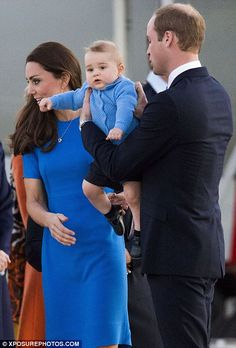 Come to daddy: Prince William carried baby George after Kate held him while walking off their plane