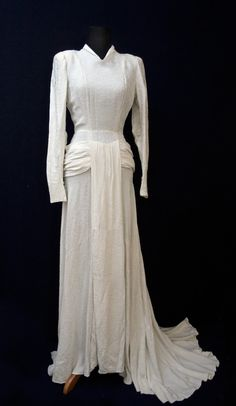 """This amazing dress was chosen by The Vintage Club as one of the top ten wedding dresses on the internet. It comes with the hand-written label that says, """"robe mariee Mamie (Jeannine) 1947"""" In other words, it was Aunt Jennie's wedding dress. Thick, beautifully draped and crafted, the beauty of this dress is in its design and construction.  One other thing that I find fascinating about this dress is that it came from France and was worn in 1947, right after the war ended. Supplies, at the…"""