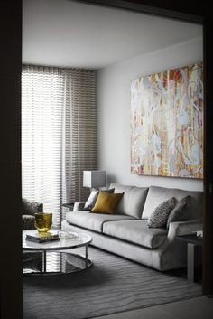 Love the size of the art here, round glass coffee table is nice and the classic gray sofa.  Draperies give the light a lovely filtered effect.
