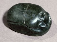 Green porphyry heart-scarab; clypeus marked; elytra marked with triple suture; eight rows of Hieroglyphic text on base.