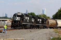 NS local crew works a spur in Charlotte, NC with the skyline of the Queen City in the background. NS is an EMD rebuilt from NS It was originally built for the Southern Railway Train Truck, Southern Railways, Railroad Photography, Norfolk Southern, Charlotte Nc, Locomotive, Trailers, Skyline, Queen