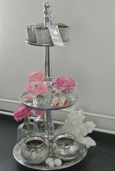 Flowers and candles on an elegant silver cake stand.