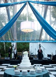 Clear tent and cafe lights for a reception.  Black and white checkerboard floor