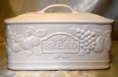 White Ceramic Bread Box Canister w/Lid Embossed Fruits  This is a beautiful white ceramic bread box ... canister style with lid. It has a raised