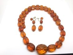 VINTAGE AMBER DEMI PARURE CONSISTING OF 14K GOLD SCREW BACK EARRINGS AND A 24 INCH NECKLACE WITH FACETED BEADS THAT GRADUATE IN SIZE.