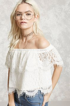 A knit eyelash lace off-the-shoulder top featuring a smocked neckline, short sleeves, a cropped silhouette, and scalloped trim.