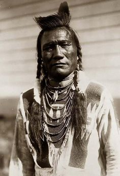 Bird Rattle, a Native American man. It was made in 1909 by Edward S. Curtis. The illustration documents a Half-length portrait of this Indian man, facing front, wearing beaded buckskin shirt, with one...