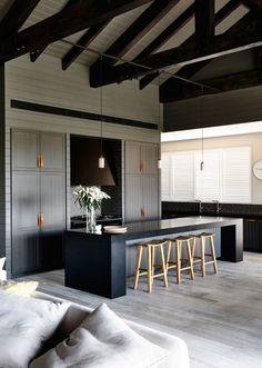 lambris bois massif, bar de cuisine noir et tabourets hauts en bois clair