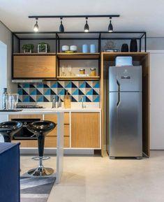 Cozinha totalmente integrada ao estar. Apenas uma bancada alta delimita os ambientes. Os armários altos com estrutura metálica aparente deixaram a atmosfera bem descontraída. Projeto Jeh Aidan e