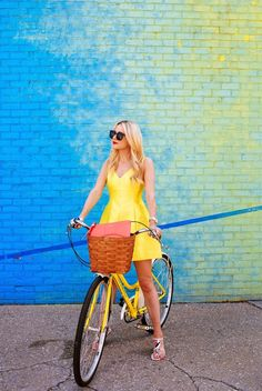 Browse these blogger-approved ways to pose with a bicycle at @Stylecaster | @atlanticpacific in yellow day dress, multicolored sandals
