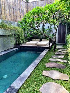 tight backyard pool with a stone edge