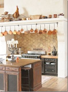 terra cotta tile backsplash. copper pots