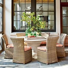 Beach House Outdoor Dining Room | Instead of using matching sets of furniture, this outdoor dining area features a comibnation of textures such as wicker, stone, and wood for a more relaxed, natural look.