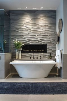 Outstanding Bathroom Tile Idea – Install 3D Tiles To Add Texture To Your Bathroom | Wavy tiles behind the bathtub and surrounding the built in fireplace create a feature wall that can also double as art. The post Bathroom Tile Idea – Install 3D Tiles To Add Texture To Your B ..