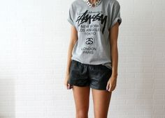 Look do Dia = Camiseta com Estampa de Texto +   Shorts de Couro Preto +  Colar de Correntes