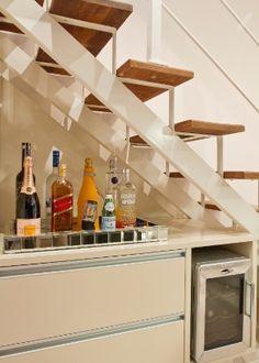 Sob a escada, a arquiteta Camila Klein propôs um bar que inclui um nicho para adega