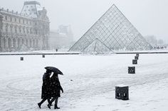 Stunning Snow Covered Destinations Around the World  Musée du Louvre and I. M. Pei's Pyramide du Louvre, Paris.
