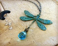 love this. (brass dragonfly is hand altered with a patina finish and combined with an african wedding glass drop)
