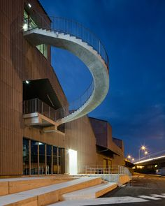 A curving concrete staircase protrudes from warehouse-like circus school in France.