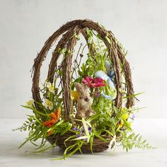 With natural elements like sisal, twigs and grass, our egg-shaped topiary brings a bit of an enchanted garden into your home for all to enjoy. Realistic flowers and butterflies surround our friend the bunny in a scene that could have come right out of a nostalgic storybook.