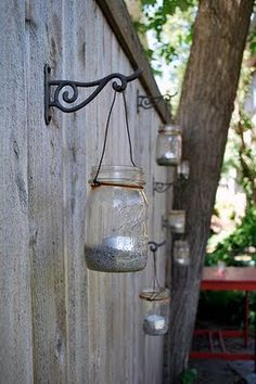 or indoors. a pretty use for coat hooks in summer. i like the Victorian iron curlique with the rustic jar. maybe leather to tie it on, and definitely a prettier candle in there.