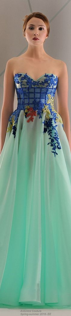 2016 - Long strapless gown with Blue sequin checkered pattern on bodice and floral pattern at waist, trailing down to a pale green flowing skirt. Antonios Couture