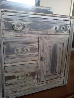 little antique commode, or dresser, sideboard etc. embossed flowers on wood.  Stripped, refinished with multiped paints and stains. Brass pulls aged to a turquoise color.