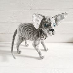 Crochet sphynx cat has all poseable paws and deep blue eyes. Grey body and big ears.