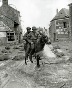 Two U.S. soldiers, Pfc William Jackson and T4 Joseph King (1st Infantry Division) are sitting on a donkey. 8th July 1944. In the background is a billboard advertising the furniture store of Julien Lenoir, a collaborateur of the Gestapo in Caen. The village was liberated on June 13 at 09:00 a.m. by F Company of the 26th Infantry Regiment of the 1st Infantry Division with support from the 743rd Tank Battalion against the German Infantry Division 277.