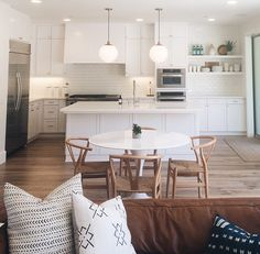 White kitchen with wood flooring, pendants and open shelving. Open floor concept.