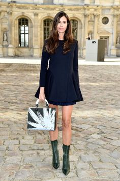 Christina Pitanguy toughened up her mini with a pair of forest-green mid-calf boots by Dior at the Christian Dior show as part of the Paris Fashion Week Womenswear Fall/Winter 2015/2016 on March 6, 2015 in Paris, France.