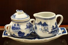 """Blue and white ceramic creamer, sugar bowl, and tray in a beautiful Asian pattern (3-piece set). The sugar bowl has a lid with a charming butterfly finial. Details: - The tray measures about 9"""" wide."""