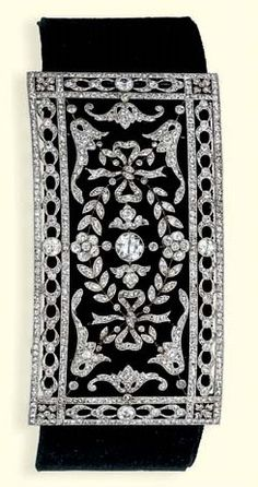 A BELLE EPOQUE DIAMOND CHOKER NECKLACE. Designed as a curved rectangular panel with central circular-cut diamond to the floral and ribbon surround and line border, later black velvet neckband, circa 1905, 7.8 cm. long. #BelleÉpoque #antique #choker