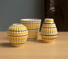 Made by Hornsea Pottery between 1961 and these colourful little pots are from the Rainbow range. The fluted yellow bodies are decorated in hand applied horizontal bands in black, red, grey and pale blue.