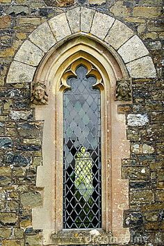 Architectural detail close up of a gothic arched church window with stone faces each side and clear leaded glass.