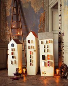Calendrier de l'avent en forme de maisonnettes en carton aux fenêtres remplies de merveilles