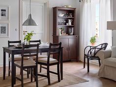 Espaço de refeição com uma mesa de refeição em preto-castanho e cadeiras com…
