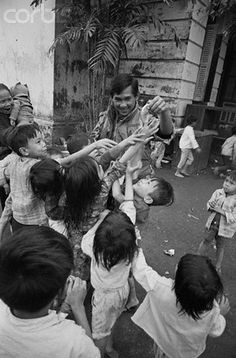 Hue 1968 - Children Laugh Where Guns Roared | Hue, South Vietnam:  Marine Sgt. Jim Colton of Tewksbury, Mass., plays with a group of Vietnamese children at the University of Hue, which has been turned into a refugee center to handle persons displaced by the recent fighting in this ancient city.  Colton is with the Headquarters Battalion, 1st Marine Division Service Company. --- Image by © Bettmann/CORBIS