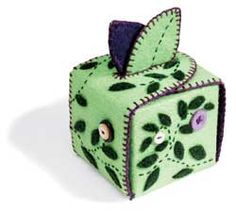 Felt box: two pieces of contrasting felt adorned with buttons, felt applique, and embroidery. When finished it folds into a little box. A piece of lightweight bukram sandwiched between the two pieces of felt makes it sturdy enough to stand. (Box template at this link)