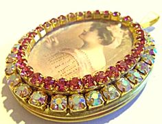 $69 Large goldtone locket with acrylic oval center depicting a beautiful lady in pink holding a vanity mirror. The cameo is surrounded by 2mm deep rose rhinestones and another row of larger 4mm aurora borealis rhinestones. The interior can hold 2 photo's