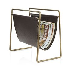 Linear in design and rich in materials, this magazine rack suspends a sling of warm brown leather from a simple frame of brass-finished iron.