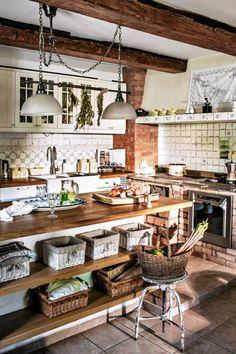 Rustykalna kuchnia. Odkryte belki stropowe, postarzane kafelki ceramiczne i cegły to kolejne atrybuty podkreślające klimat domu.