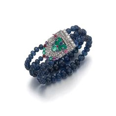 Gem set and diamond bracelet, 'Tutti Frutti', Cartier, circa 1935. Of geometric and foliate design, composed of three rows of sapphire beads, the clasp set with carved and cabochon emeralds, cabochon sapphires, rubies and amethysts, square-, circular- and single-cut diamonds.