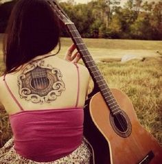 Beautiful guitar tattoo on the back. Only a part of the guitar and its strings are inked in the tattoo. It forms a cute looking circle on the base of the neck still emphasizing that it is a guitar.