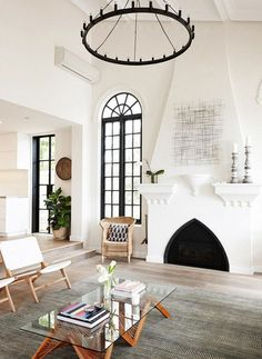 Cozy living space with a fireplace, a rustic chandelier, a simple rug, and woven armchair