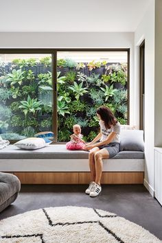 """Homeowner Lauren relaxes with baby Vivienne on a custom window seat. """"It gives the room personality,"""" says architect Ben. Through the window is a <a href=""""http://pippisplants.com/"""" rel=""""noopener"""" target=""""_blank"""">Pippi's Plants</a> vertical garden. """"We had it installed because it was too much fence to look at out the window,"""" says Lauren. Photography by Nikole Ramsay. Styling by Emma O'Meara"""