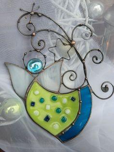 Anděl s hvězdičkou Výrobek je určený k zavěšení jako dekorace do oken nebo volně na stěnu. Vyrobeno z barevného skla,použita technika fusing a doplněno ornamenty z patinovaného drátu.Velikost 135x185mm