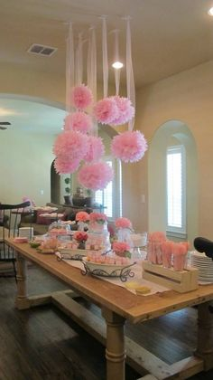 COULD THIS IDEA BE ADAPTED? Maybe flowers, streamers, paper lanterns, pompoms could be attached to a round wreath in advance then suspended over each table. How about gathering the streamers together under the wreath and then let the tailing streamers puddle onto the table. You could then keep the table decor low and simple with votives,  flourescent green and hot pink confetti interspersed with the odd flower on the black table cloths with black and white striped napkins?