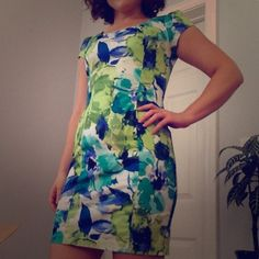 Blue and green floral print mini dress Form fitting with a slight stretch. Colors are vibrant green, teal and Aqua in the floral print. Measures 32 inches in length with small slit in back of the skirt. Has belt loops but does not come with a belt. Zips up the back. Iz Byer Dresses Mini